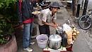 Komplett utcai konyha és megilletõdött tulajdonosa. A faszínû kockák fõtt rizst rejtenek.